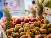kiwien en ananas bij de open markt Royalty-vrije Stock Afbeeldingen