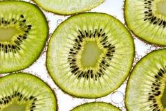 Kiwifruchtscheiben, die in Sodawasser schwimmen Stockfoto