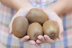 Kiwifruit in de hand van de vrouw Stock Foto's