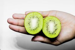 Kiwifruit Healthy eating and diet Topic Human hand holding a half kiwi isolated on a white background in the studio. Background diet eating half hand healthy stock photography