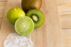 Kiwifruit and lemon with salt on wood cutting board Stock Photography