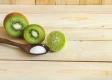 Kiwifruit and lemon with salt on wood cutting board Stock Photo