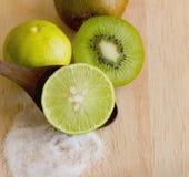 Kiwifruit and lemon with salt on wood cutting board Stock Images
