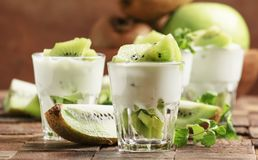 Kiwifruit met romig yoghurtdessert in glas, de oude houten achtergrond van de keukenlijst, selectieve nadruk stock fotografie