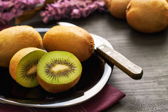 Kiwifruit served on plate. On black wooden background Royalty Free Stock Photography