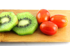 Kiwifruit slices into pieces and three Tomato. Royalty Free Stock Photography