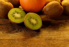 A kiwifruit split in half lies on a wooden cutting board royalty free stock image