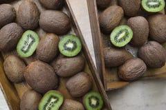 Kiwifruits i plasterki kiwi w drewnianym pudełku i pucharze obraz stock