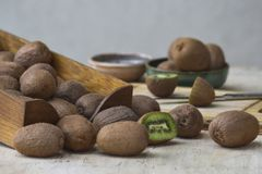 Kiwifruits and slices of kiwi in a wooden box and a bowl. stock photo