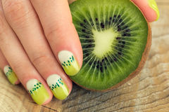 Kiwil art manicure. Kiwi and skin care of a beauty female hand with green and white moon nail art manicure on a wooden background royalty free stock photography
