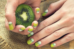 Kiwil art manicure. Kiwi and skin care of a beauty female hands with green and white moon nail art manicure on a sackcloth and wooden background stock photo