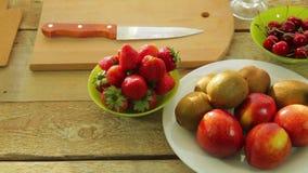 Kiwin, persikor, jordgubbar och körsbär för ny frukt är på en trätabell lager videofilmer