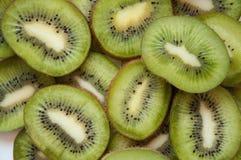 Kiwin skivade gr?n bakgrund Massor av gr?na tropiska frukter Klipp kiwin in i stycken royaltyfri fotografi