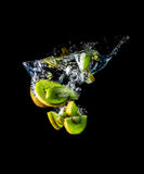 Kiwiplakken die in het waterclose-up vallen die, macro, plons, bellen, op zwarte worden geïsoleerd Stock Fotografie