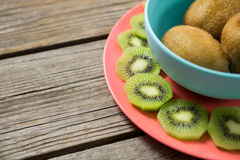 Kiwis arranged in bowl and plate on wooden table. Close-up of kiwis arranged in bowl and plate on wooden table stock photos