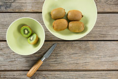 Kiwis in bowl with knife on wooden table. Overhead of kiwis in bowl with knife on wooden table stock images