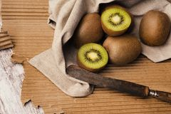 Kiwis in brown table. Green kiwis in brown table and paperboard stock image