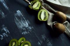 Kiwis in dark background textured Stock Photos