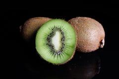 Kiwis de kiwi et demi kiwi sur le fond noir Photo de studio Images libres de droits