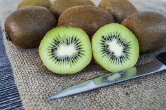 Kiwis, deux morceaux de kiwi avec le couteau, kiwi se tenant sur le plancher en bois Image stock