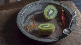Kiwis divisés en deux avec le piment rouge dans la cuvette de cuivre superficielle par les agents Images stock