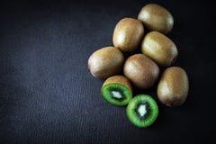 Kiwis entiers mûrs et demi kiwis sur le béton noir s Photographie stock libre de droits