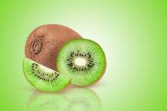 Kiwis entiers mûrs et demi kiwis sur le fond vert Images stock