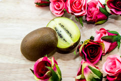 Kiwis. Ipe kiwi cut into two pieces, with flowers placed around royalty free stock images