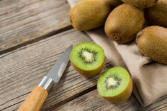 Kiwis with knife on wooden table. Close-up of kiwis with knife on wooden table royalty free stock image