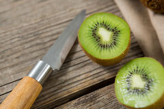 Kiwis with knife on wooden table. Close-up of kiwis with knife on wooden table stock photos