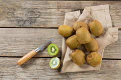 Kiwis with knife on wooden table. Overhead of kiwis with knife on wooden table royalty free stock images