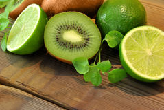 Kiwis and limes. On a wooden table stock images