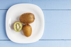 Kiwis madurados en la placa blanca y en la tabla de madera para la comida vegetariana Visión superior Copie el espacio Foto de archivo libre de regalías