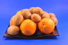 Kiwis and oranges. Oranges and kiwi fruit on a brown plate on a blue background royalty free stock photo
