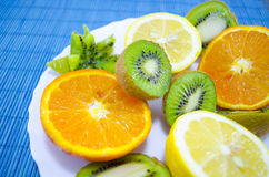 Kiwis, oranges and lemons on a plate. Fruit dessert on a plate royalty free stock images