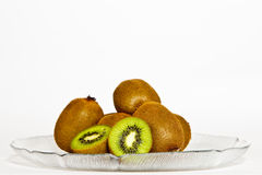 Kiwis in a plate. Some Kiwis, with a sliced Kiwi in front, in a plate royalty free stock photo