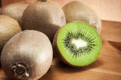Kiwis on a rustic table. Rustic image of a bunch of kiwi fruits with one of them sliced in half showing the delicious green interior and the seeds stock photography