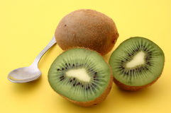 Kiwis with spoon on yellow. A composition of three pieces of kiwi fruit with a teaspoon on bright yellow background stock images