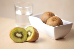 Kiwis and water on a table Stock Photography