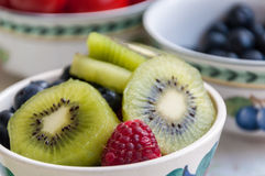 Kiwis and wild berries in a bowl. Several bowls with kiwis and wild berries on a breakfast table royalty free stock image