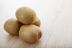 Kiwis on a wooden surface. Kiwis stacked on a wooden surface stock photo