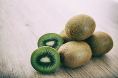Kiwis on a wooden surface. Kiwis stacked on a wooden surface stock images