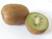 Kiwistück auf einem weißen Hintergrund mit einem ganzen Kiwifruit Stockfotos