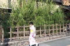 Woman in Kimono dress walking on the walkway and background bamboo tree with wooden fence. Kiyomizu, Higashiyama-ku, Kyoto Japan, November 17, 2017 : woman in Stock Photo