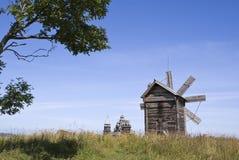 Kizhi. A windmill and Preobrazhenskiy church Royalty Free Stock Photo