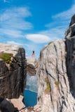 一次极端计划旅行的画象女孩的kjerag的石头的在挪威,感觉的山的  免版税图库摄影