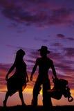Kjolen för konturkvinnahållen ser upp på cowboyen Arkivfoto