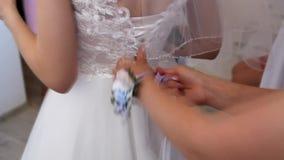 Klä bruden på bröllopdagen som binder bröllopsklänningskosnören arkivfilmer