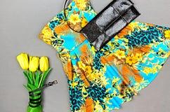 Klä med det blom- trycket, gula tulpan och den svarta kopplingen på grå färger Royaltyfri Bild