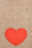 Klädd med filt röd hjärta på säckväven Arkivfoton